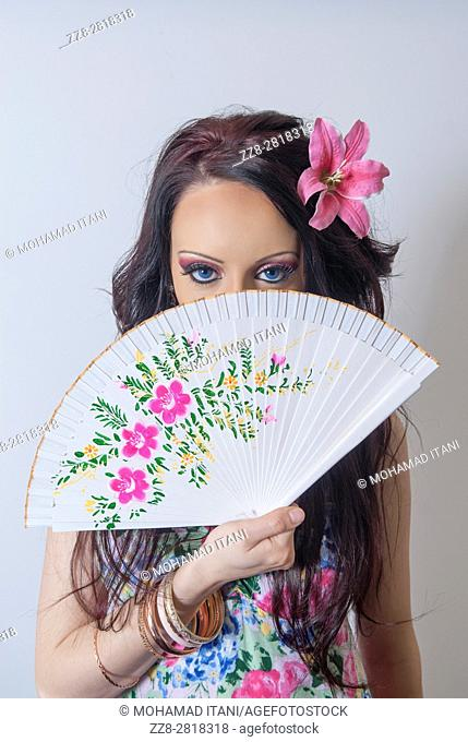 Beautiful young woman hiding her face with a fan
