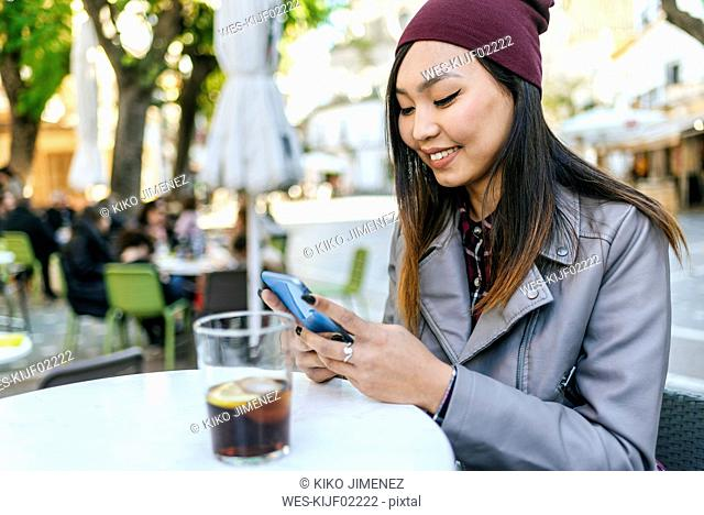 Smiling young woman using smartphone at pavement cafe