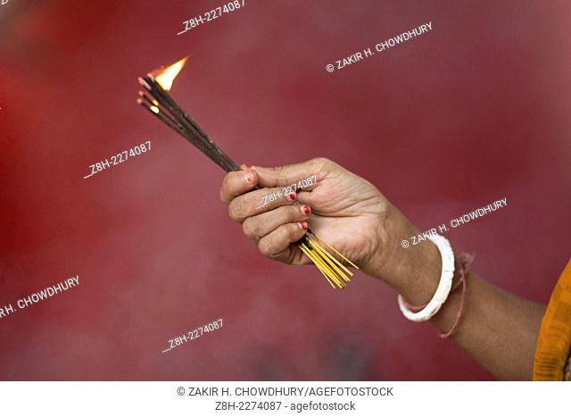 Hindu woman holding incense sticks prays at the Dhakeshwari temple during the Durga Puja festival
