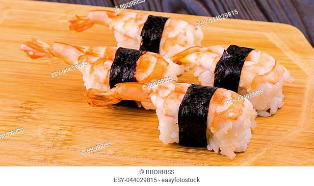 Sushi with shrimps on a wooden stand
