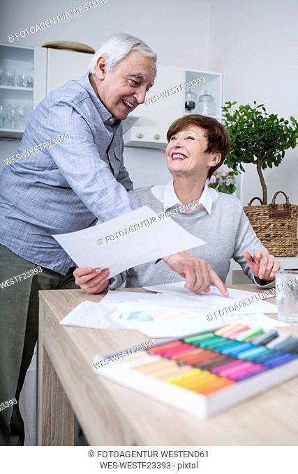 senior woman painting with crayons, husband watching