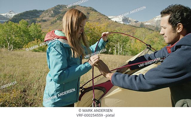 Medium panning shot of hikers assembling camping tent / American Fork Canyon, Utah, United States