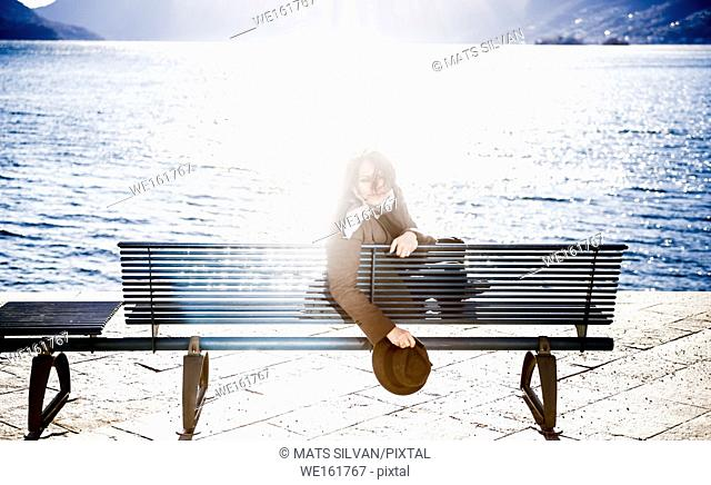 Woman Sitting on a Bench on the Waterfront and Looking Back with Sun Reflection in Ascona, Switzerland
