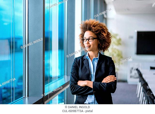 Young businesswoman with arms folded looking out through boardroom window