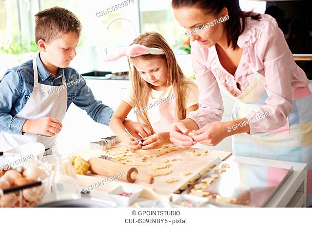 Girl, brother and mother baking easter biscuits at kitchen counter