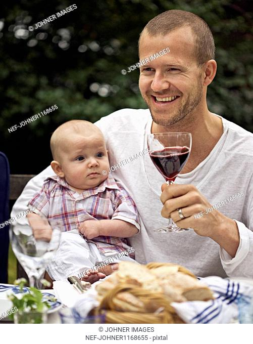 Mid adult man toasting with wine while holding baby boy