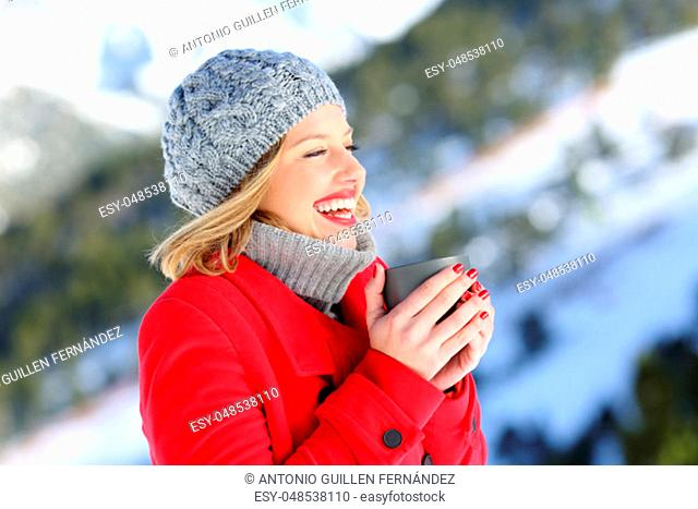 Portrait of a happy woman wearing a red coat heating with a cup of hot coffee in a snowy mountain in winter