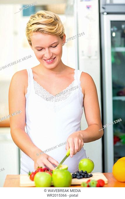 Pregnant woman cutting fruits on the cutting board