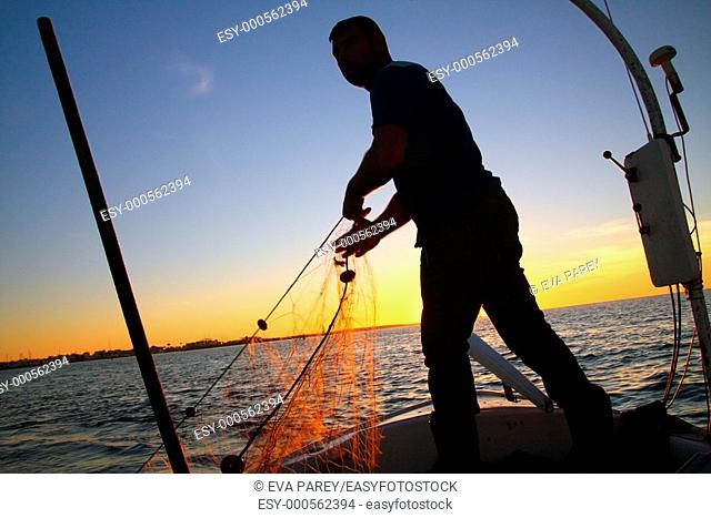 A young fisherman is thorwing the fishing net into the sea near La Savina port and in front of the Tiburon Beach in Illetas a long sandy extension of the island...