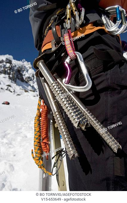 Mountaineer in snow on Mountain with ice screws and karabiner