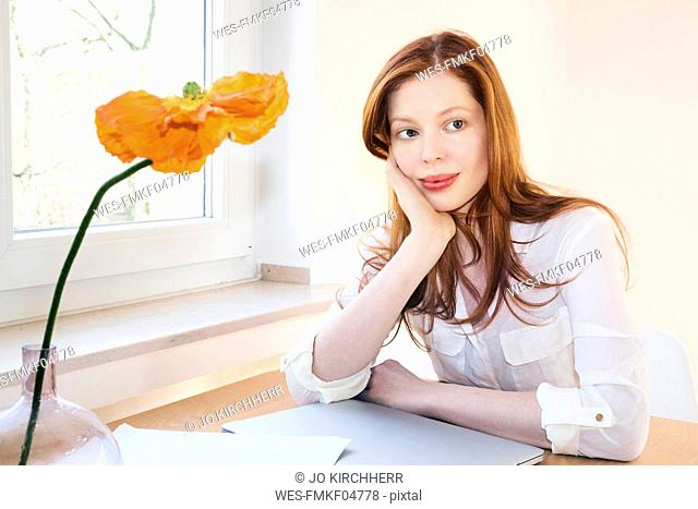 Portrait of redheaded woman at home office