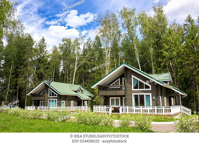 Wooden cottages with trees on background rural, Russia, Moscow region