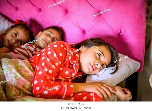 Boy and two sisters lying in bed at bedtime