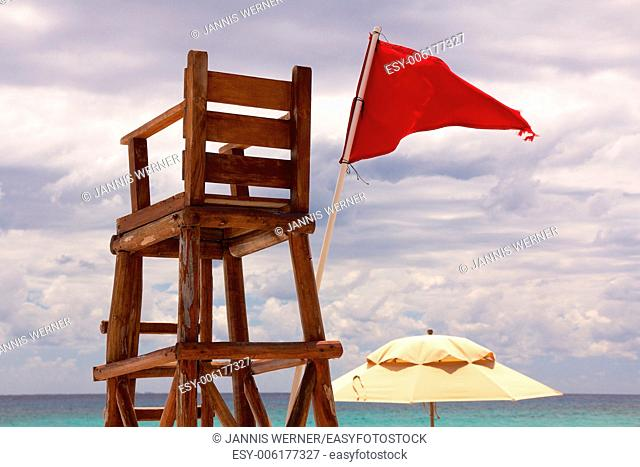 Lifeguard post at a tropical beach stands abandoned as red flag waves in the wind