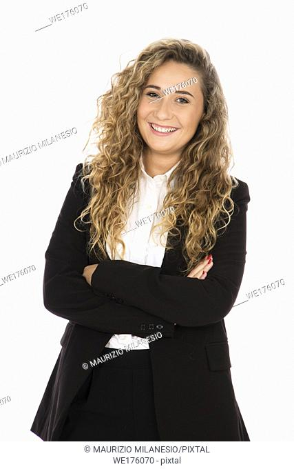 Smiling girl with curly blonde hair, she is standing with her arms crossed, wearing a black suit and white shirt