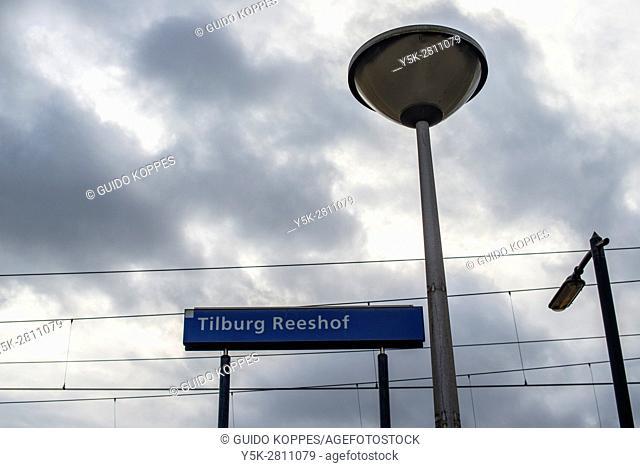 Tilburg, Netherlands. Namesign, streetlight and catenary at Tilburg-Reeshof railway station
