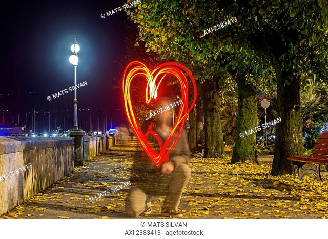 A man drawing a red glowing heart shape in the air; Locarno, Ticino, Switzerland