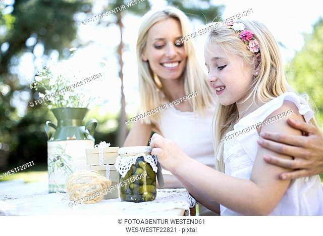 Smiling mother and daughter with preserved gherkins outdoors