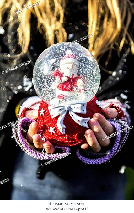 Girl's hands holding snow globe with snowman, close up