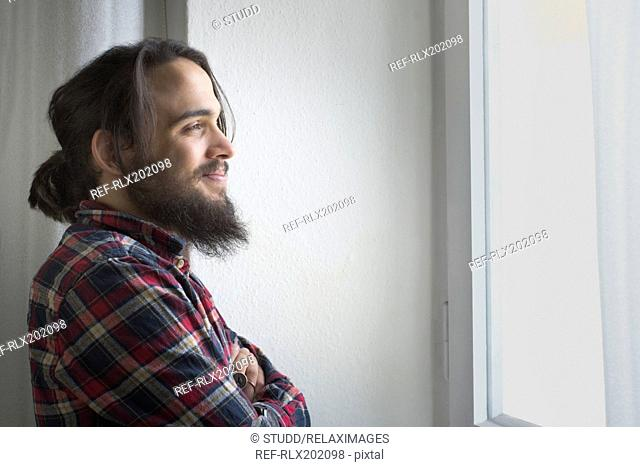 Thoughtful young man looking through window at home