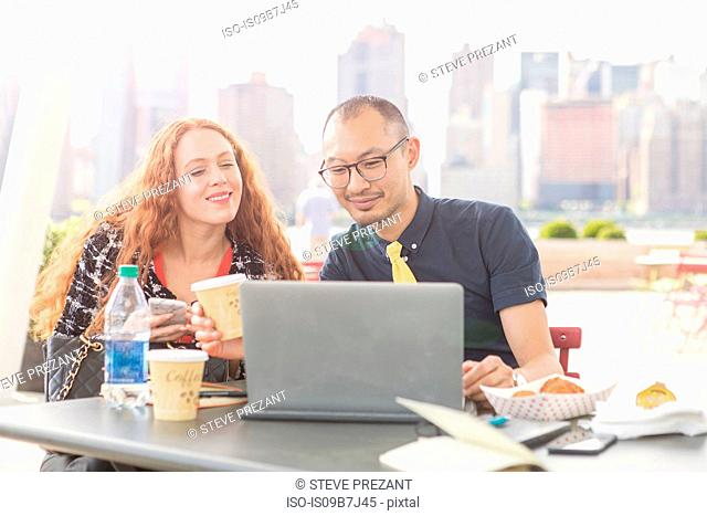 Businessman and woman using laptop at waterfront cafe table, New York, USA