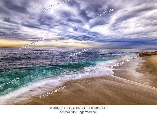 Majestic storm clouds over the ocean. Waves washing up on Casa Beach. La Jolla, California, United States