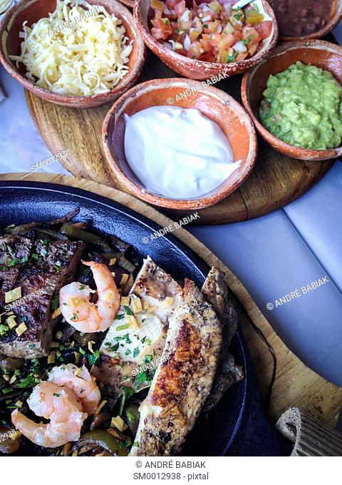 Mexican Fajita Dish with beef steak strips, shrimp and chicken served in a hot cast iron skillet next to a tray of side dishes like sour cream, refried beans