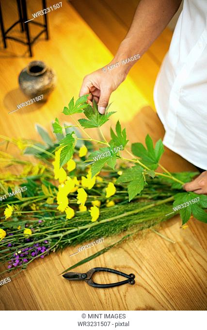 Person in a flower gallery, working on Ikebana arrangement with leaves, yellow and purple flower