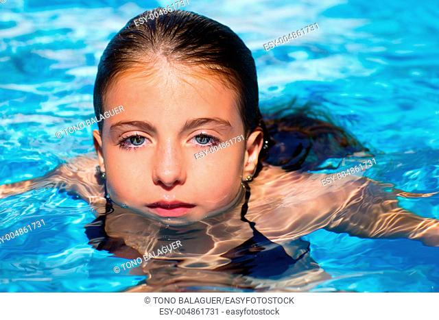 beautiful blue eyes kid girl at the pool with face in water surface