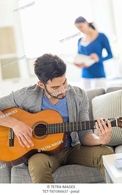 Man playing guitar, woman in background