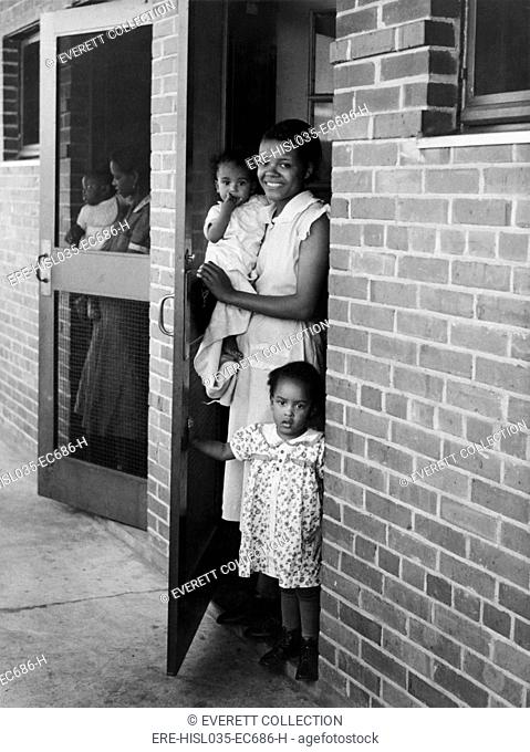 African American mothers and children at new building, March 1939. They live in the Dixie Home, a Public Works Administration project covering 42 acres of...