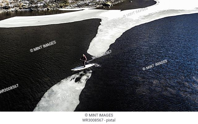 Aerial view of a paddleboarder carrying his board standing on a block of ice on an ice floe in an inlet in the Lofoten Islands, Norway
