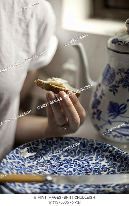 A breakfast table with a tall coffeepot and blue and white china plate. A woman sitting holding a piece of buttered bread