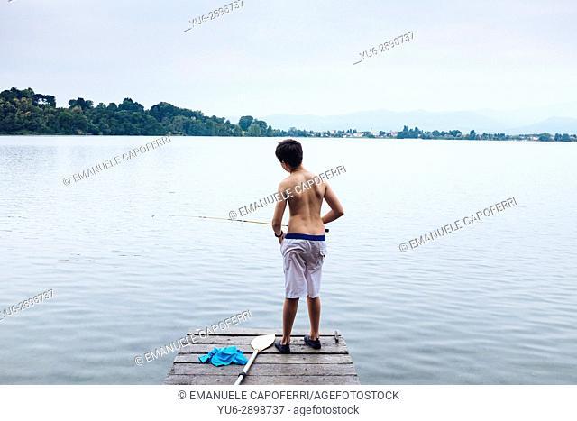 12 year old boy fishing on lake pier