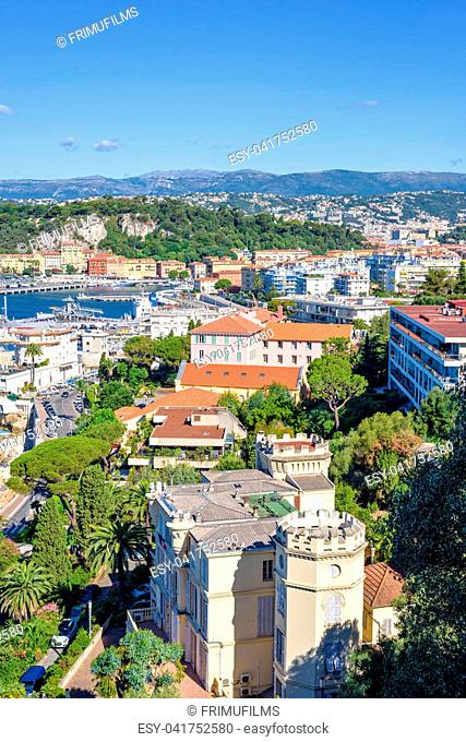 Daylight sunny view to city buildings. Bright blue sea and sky. Mountains on background. Antibes, France