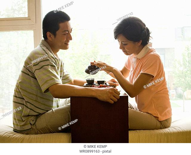 Profile of couple sitting cross legged with tea and fruit with large window in background