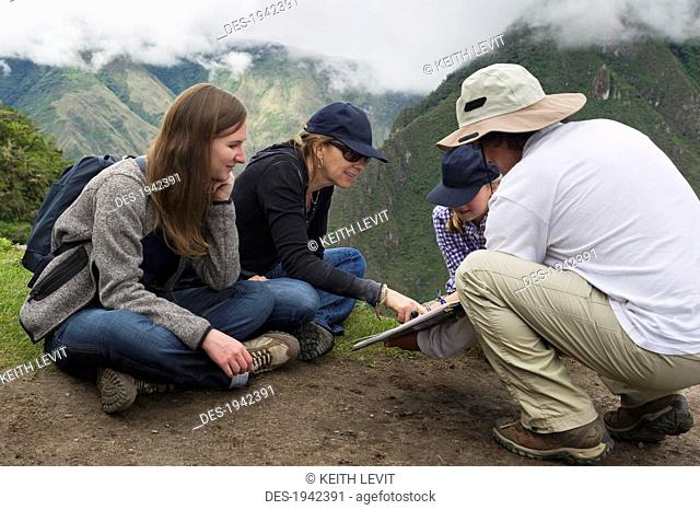 tourists read from a guide at the lost city of inca, machu picchu peru