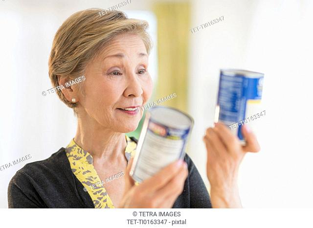 Senior woman reading labels on canned food