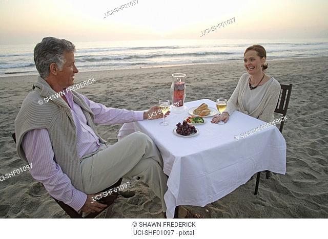 Mature couple having picnic on the beach
