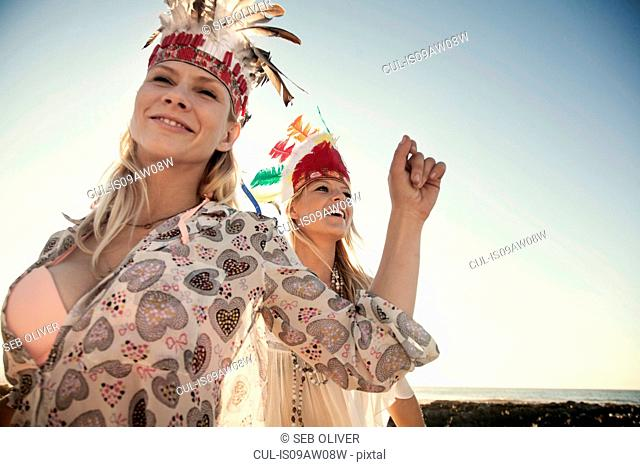 Young women wearing feather headdresses dancing, looking at camera smiling