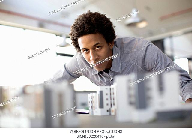 Mixed race architect examining architectural model in office
