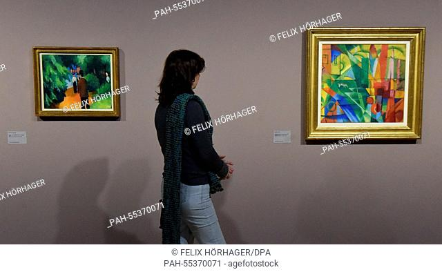 A visitor looks at the paintings 'Park by the Water' (L) (1913) by August Macke and 'Landscape with House and Two Cows' (1914) by Franz Marc during the press...