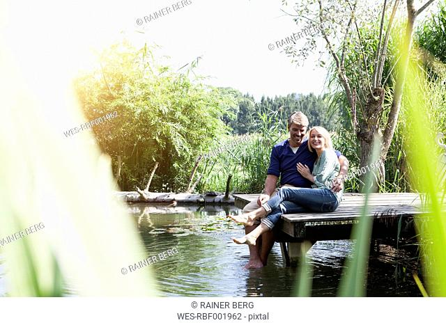 Happy mature couple sitting on jetty at a lake