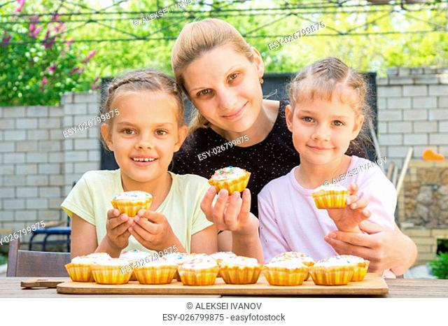 Mother and two daughters sitting at the table with Easter cupcakes in his hands and looked into the frame