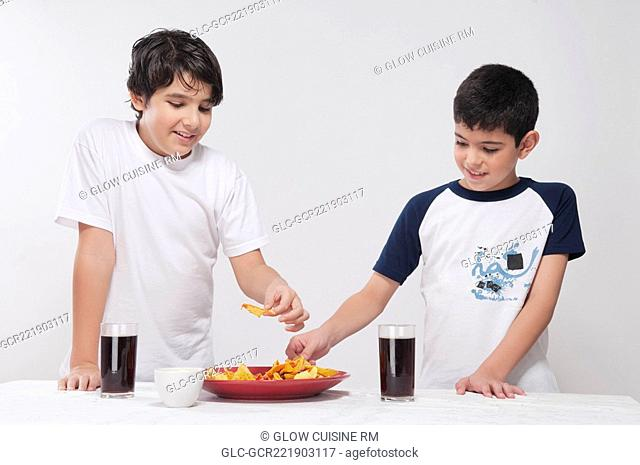 Close-up of two boys sharing a platter of nachos
