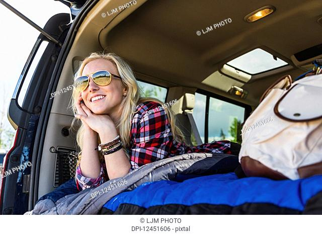A young woman on a road trip lays in the back of a vehicle with a sleeping bag looking out from the open door; Edmonton, Alberta, Canada