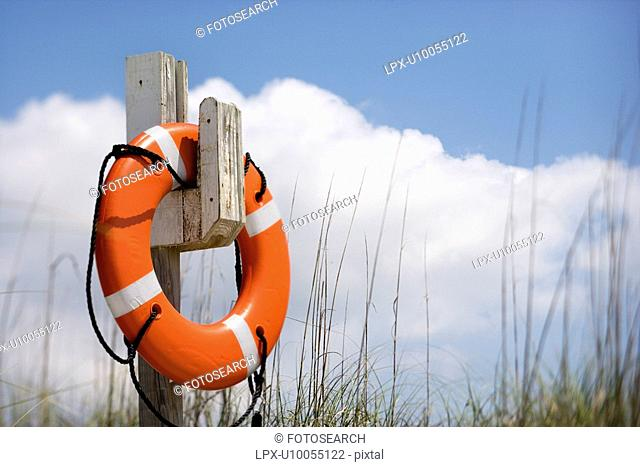 Life preserver hanging on post on beach on Bald Head Island, North Carolina