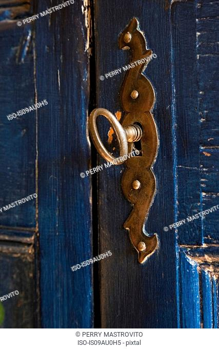Close up view of key in lock on blue wooden door