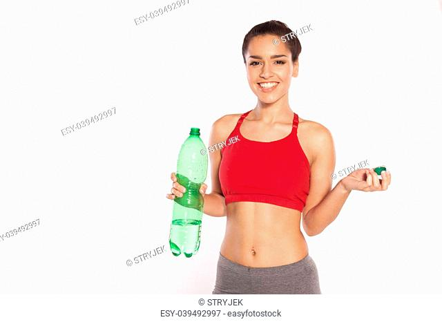 Smiling shapely young woman wearing a sports bra standing looking at the camera with a large bottle of bottled water in her hand isolated on white
