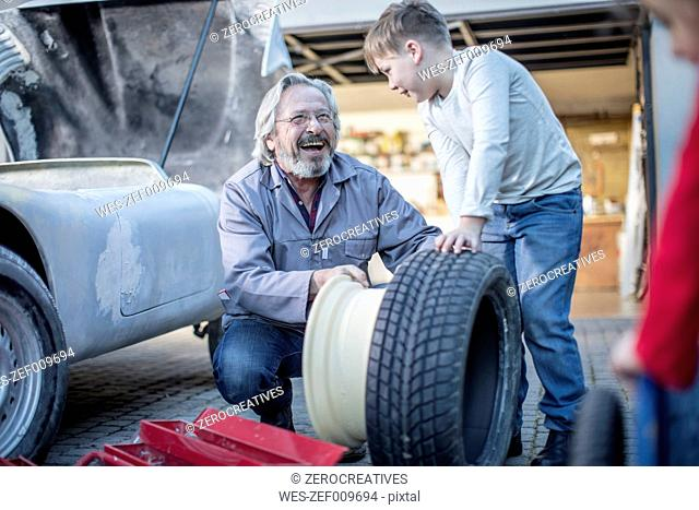 Happy senior man and boy changing car tire
